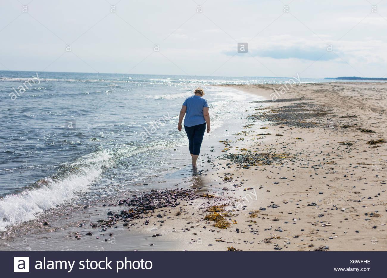 Denmark, North Zealand, Woman walking on beach - Stock Image