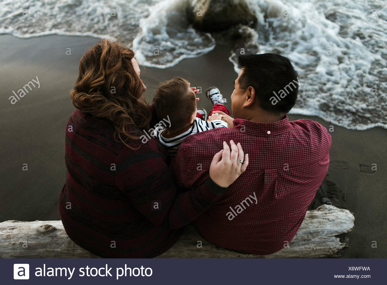 Rear view of mother and father sitting on beach - Stock Image