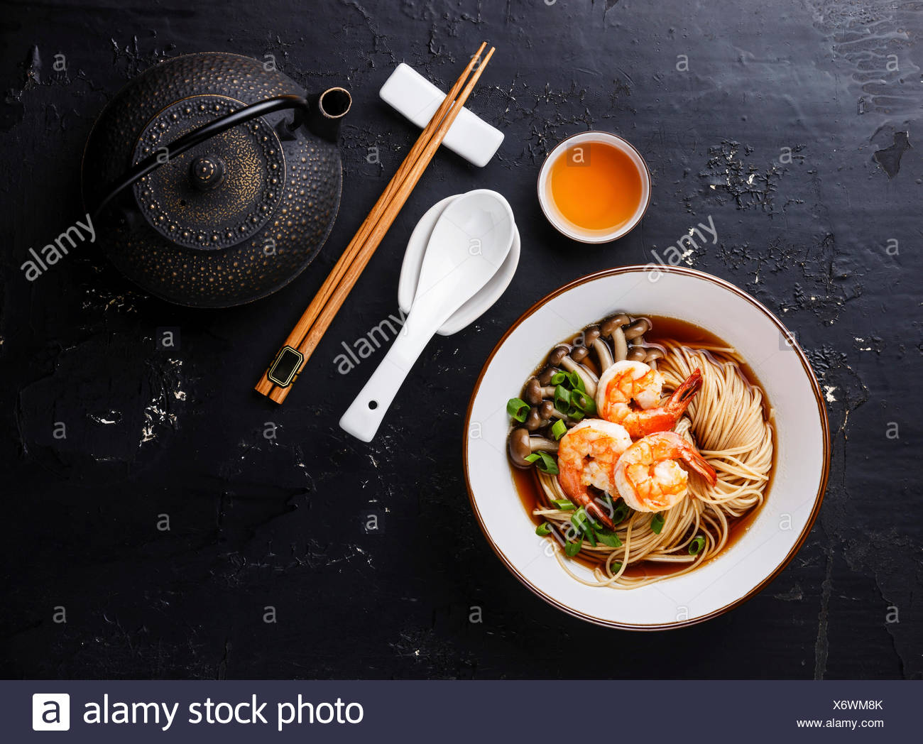 Asian Ramen noodles with broth in bowl serving size and Tea on dark background - Stock Image