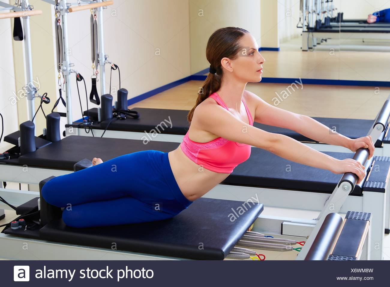 Pilates reformer woman mermaid exercise workout at gym. - Stock Image