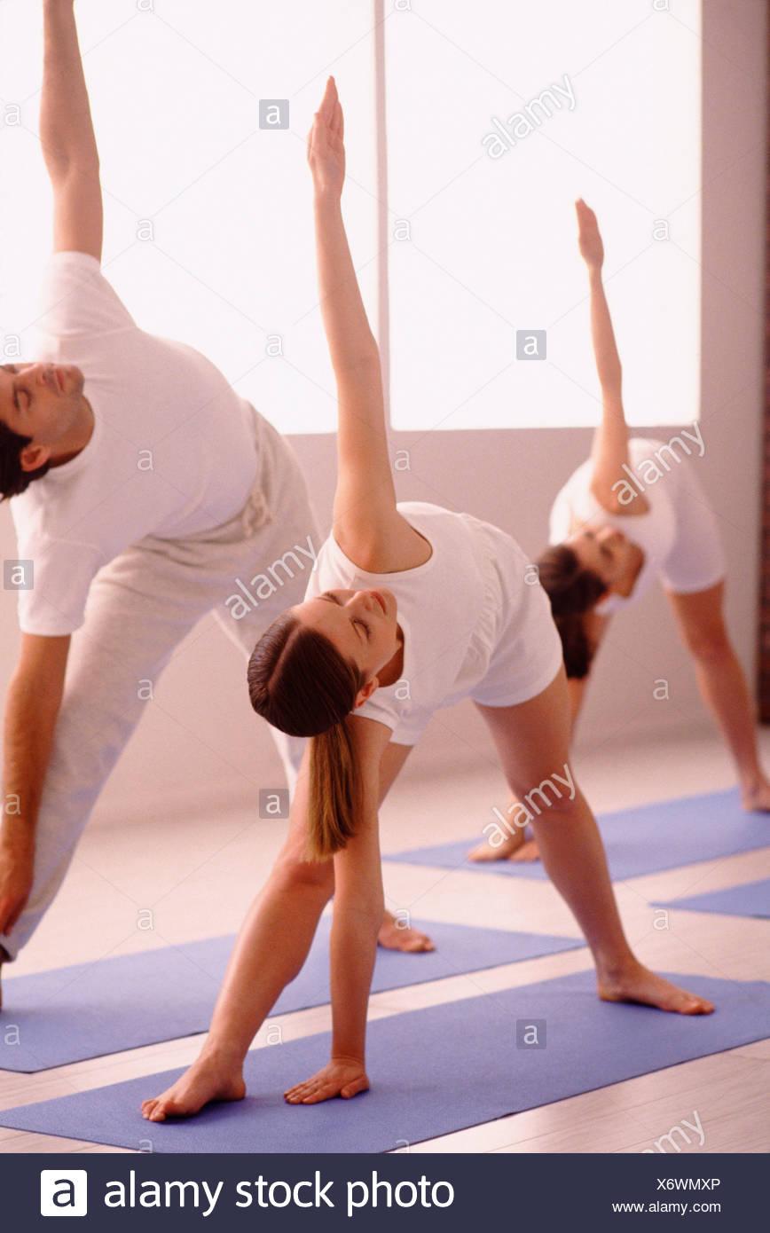 Three People Stretching On Yoga Mats Stock Photo Alamy
