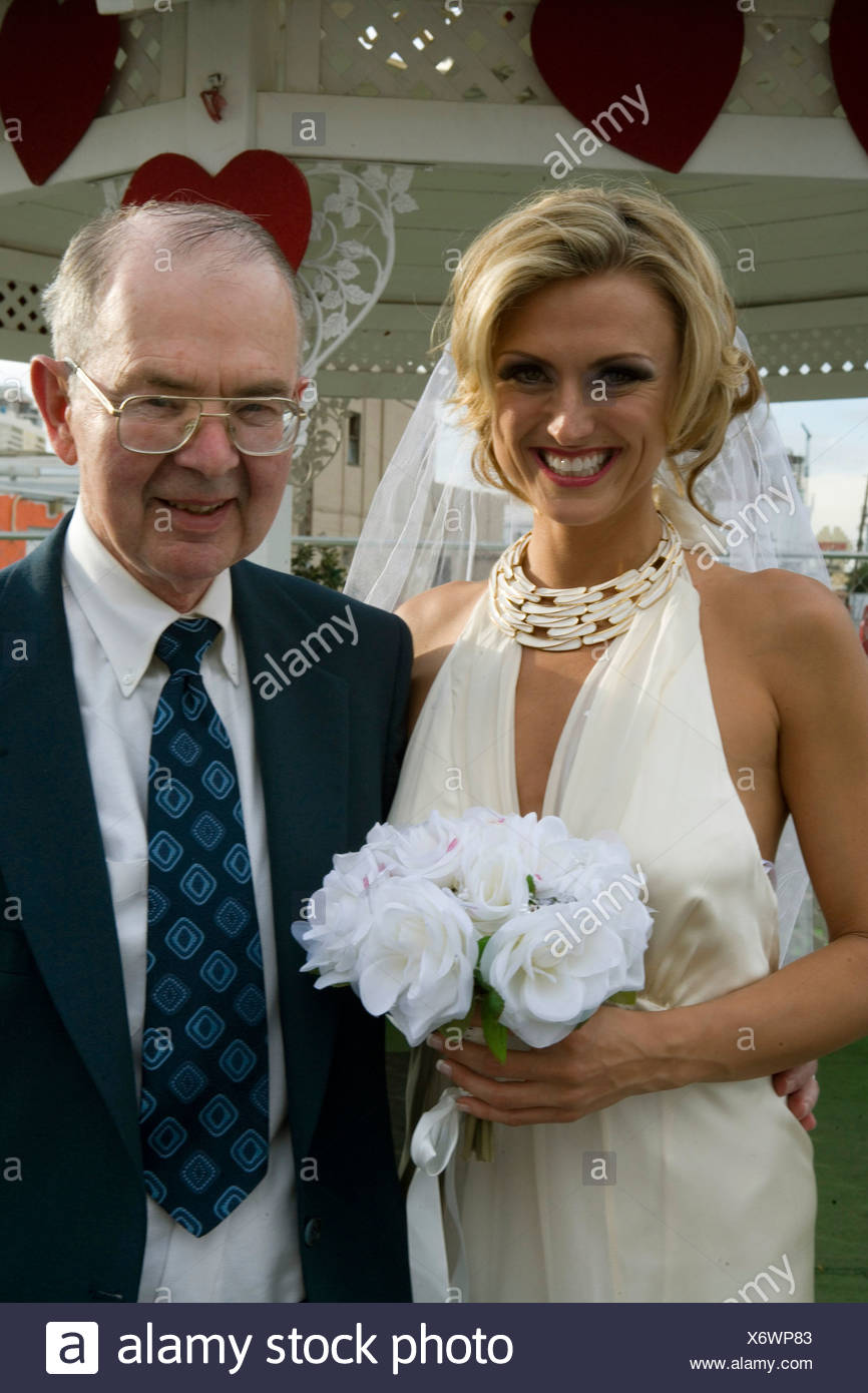 Bride standing with a senior man and smiling - Stock Image