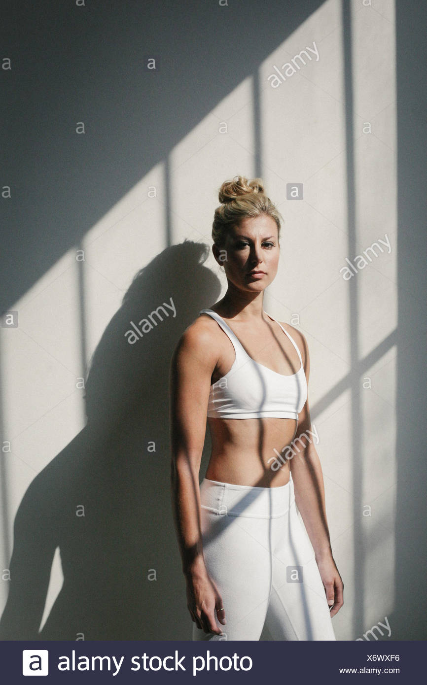 Portrait of a blonde woman, in a white crop top and leggings, standing in front of a white wall, posing for a picture. - Stock Image