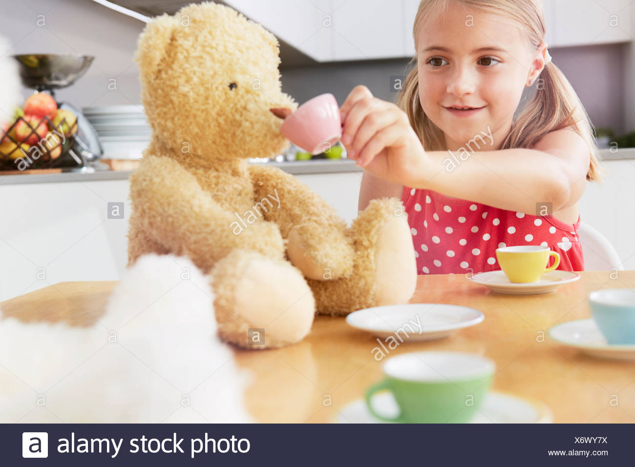 Girl having tea party with soft toys - Stock Image