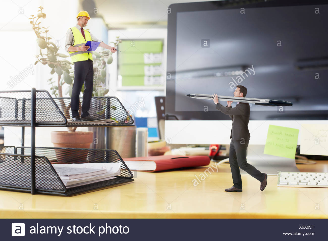 Mature foreman directing businessman carrying large pen on oversized desk - Stock Image
