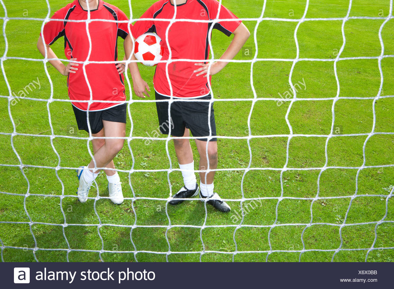 Soccer players standing at goal net - Stock Image