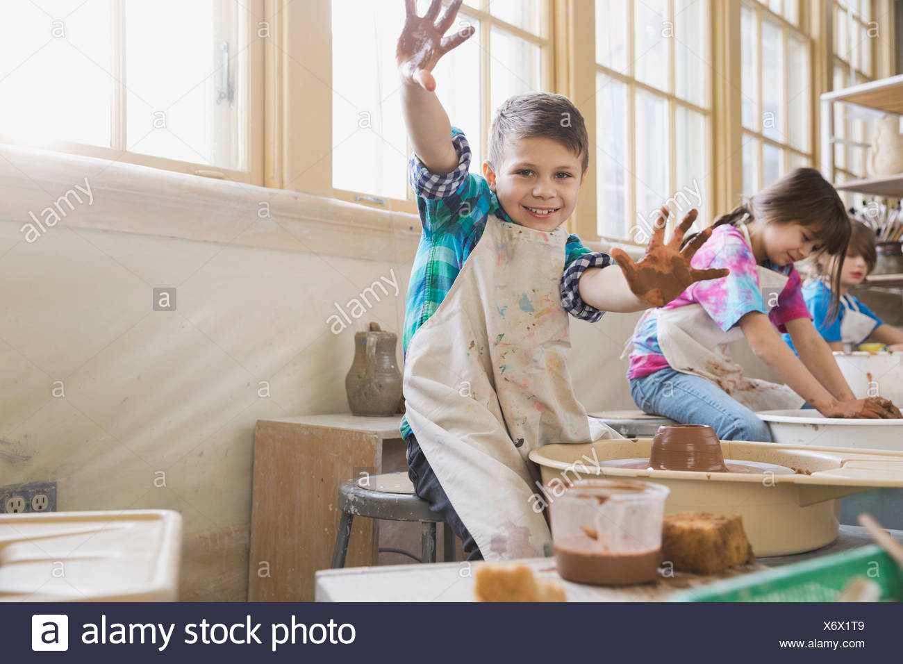 Portrait of boy showing palms in pottery class - Stock Image