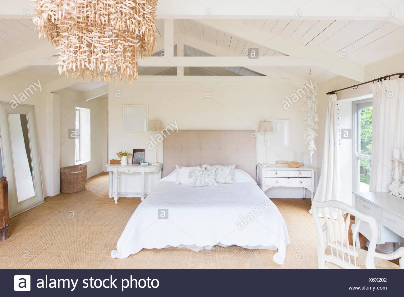 Chandelier and bed in rustic bedroom - Stock Image