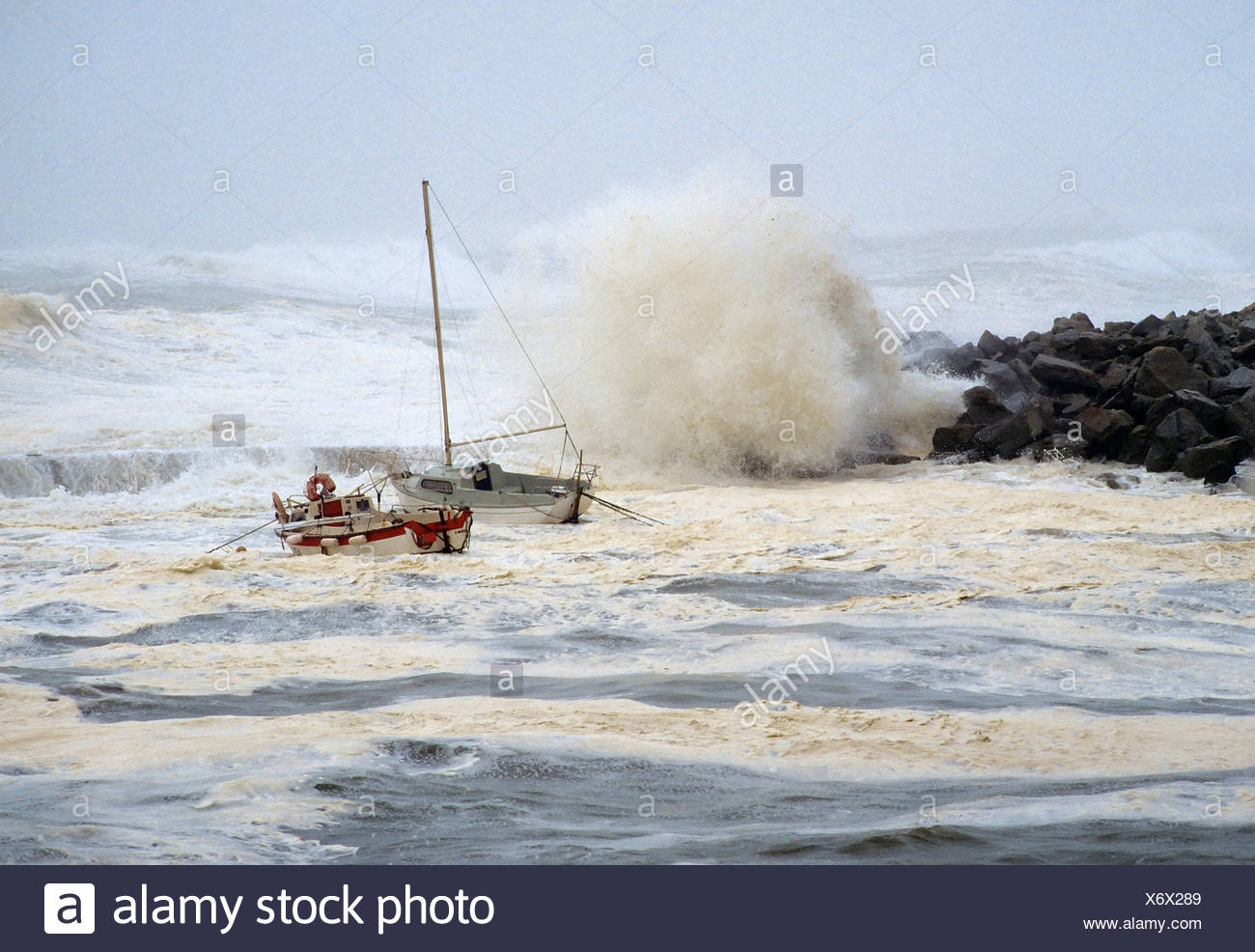 High waves crashing over rocks, rocking small boats, stormy seas on the Brittany coast, hurricane, Finistere, Brittany, France - Stock Image