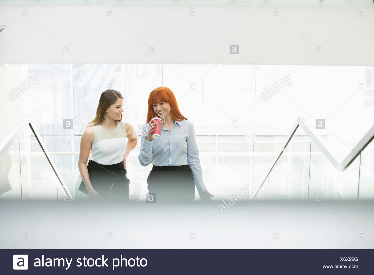 Businesswomen having coffee while moving up steps in office - Stock Image