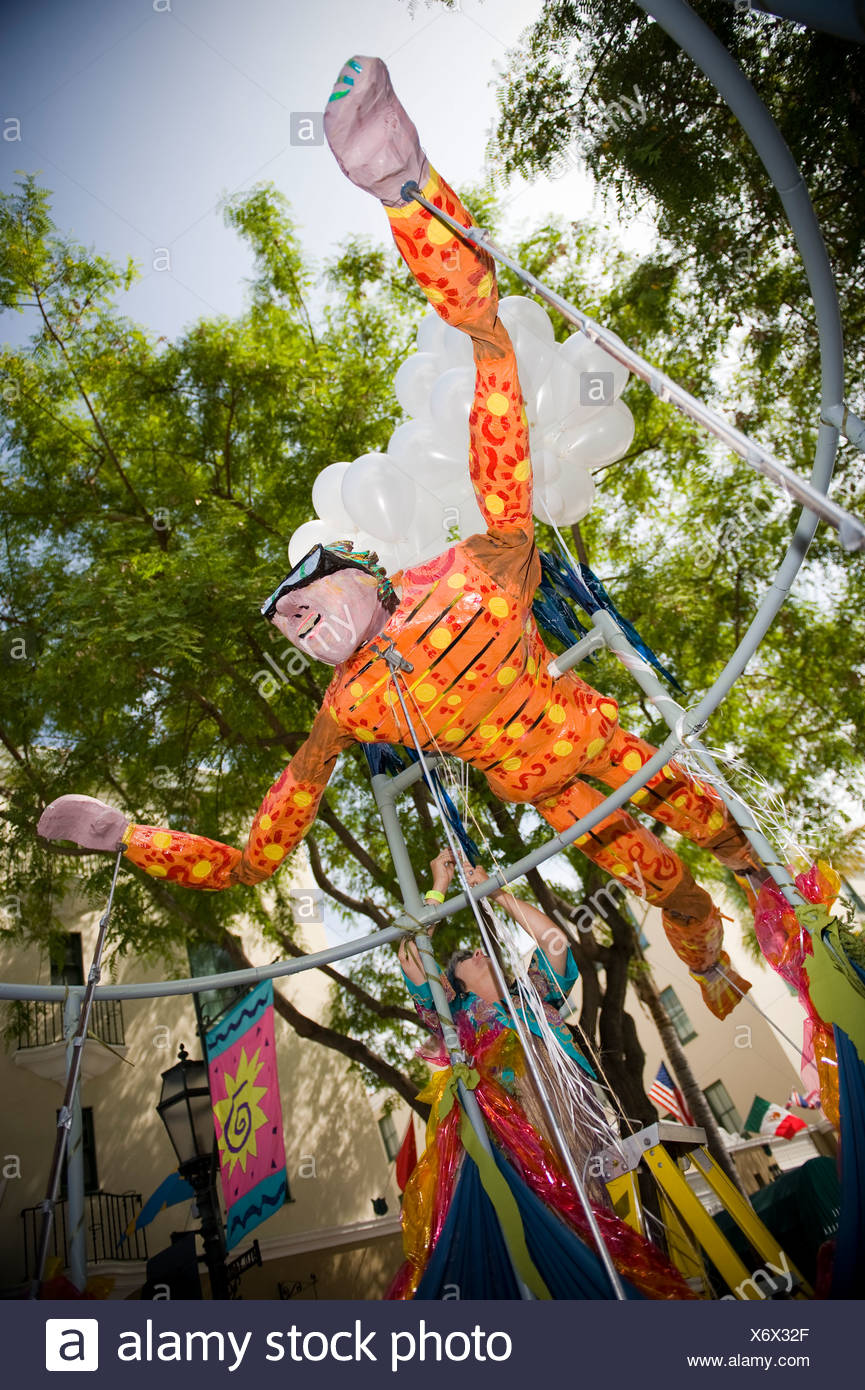 A flying man float at a parade in Santa Barbara. The parade features extravagant floats and costumes. - Stock Image