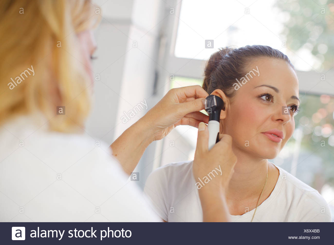 ENT physician Examining the Ear from Female Patient - Stock Image
