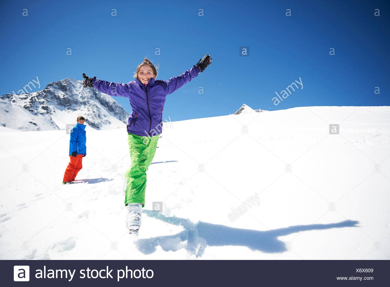 Teenager girl jumping in snow, arms outstretched - Stock Image