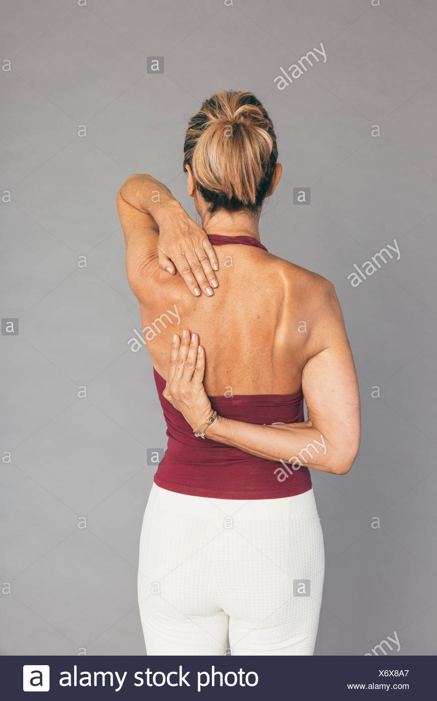 Mature woman shoulders and arms stretching exercise Stock Photo