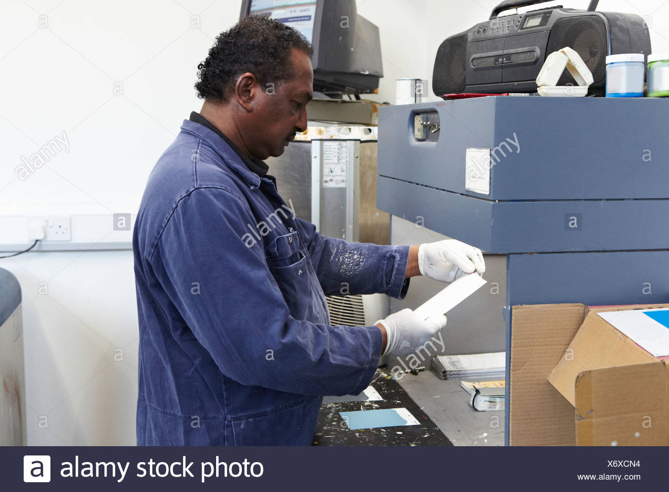 Worker matching paint to swatches - Stock Image