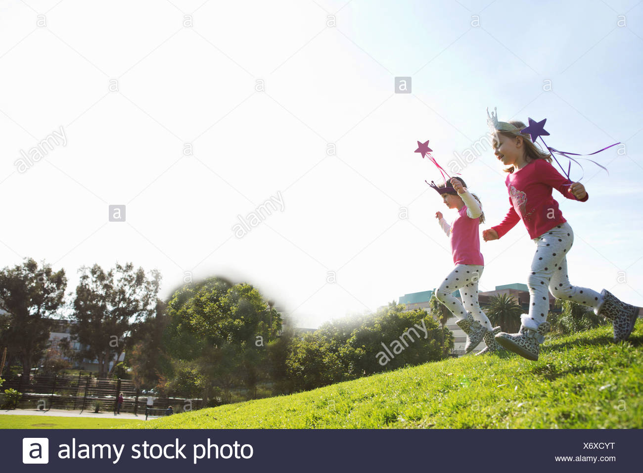 Two young sisters dressed up as fairies running down hill - Stock Image