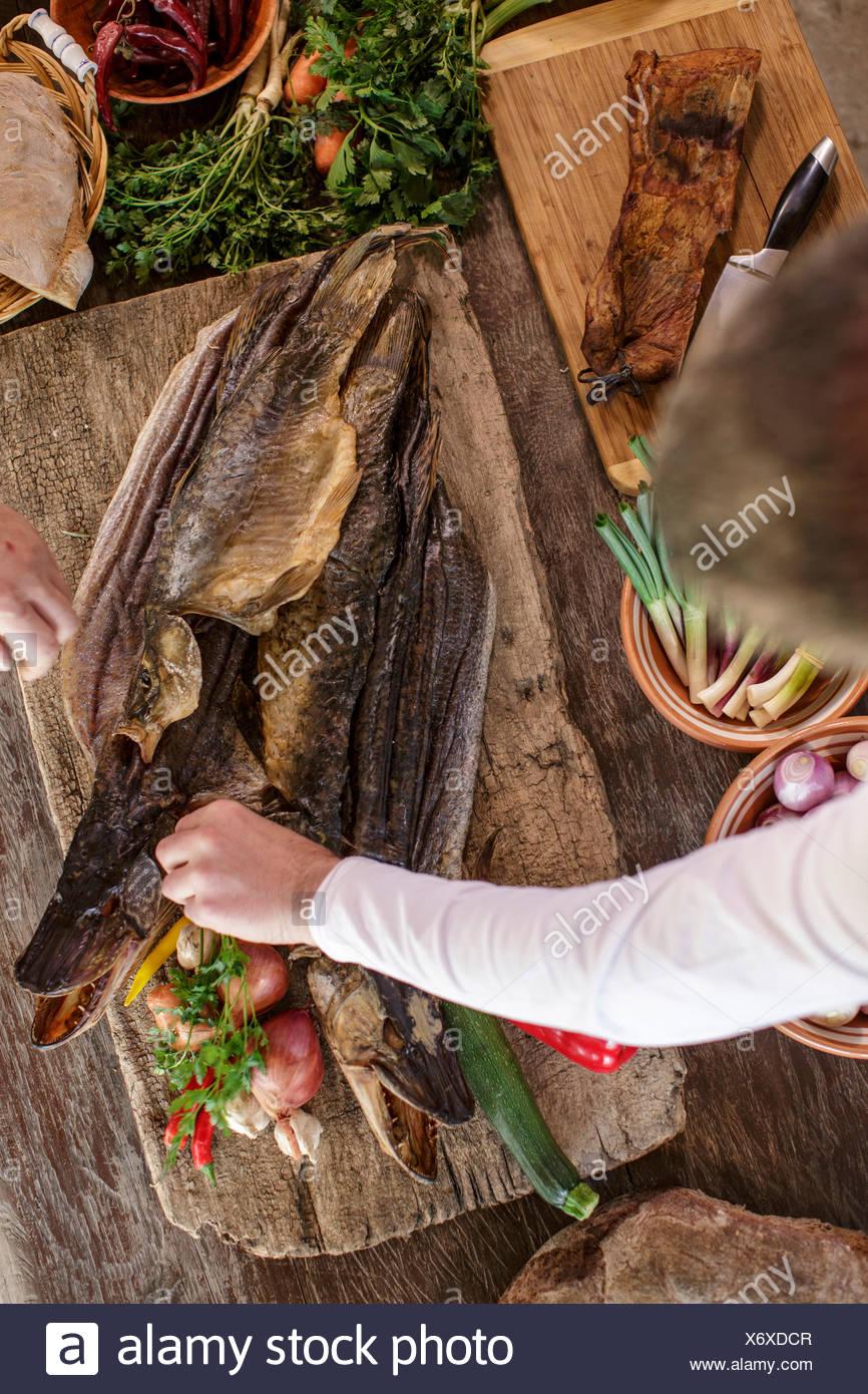 Person preparing pike on cutting board - Stock Image