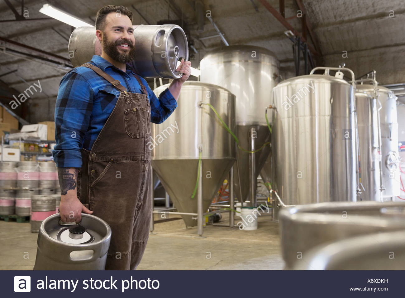 Brewery worker carrying quarter slim kegs - Stock Image