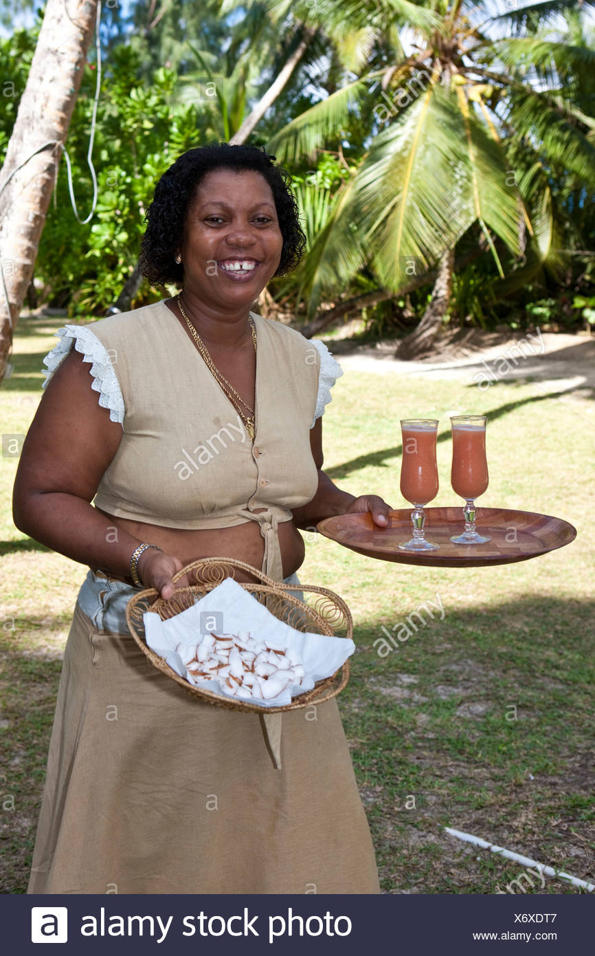 Creole woman serving drinks on Anse Goumement near Pointe Lazare, Mahe Island, Seychelles, Indian Ocean, Africa - Stock Image