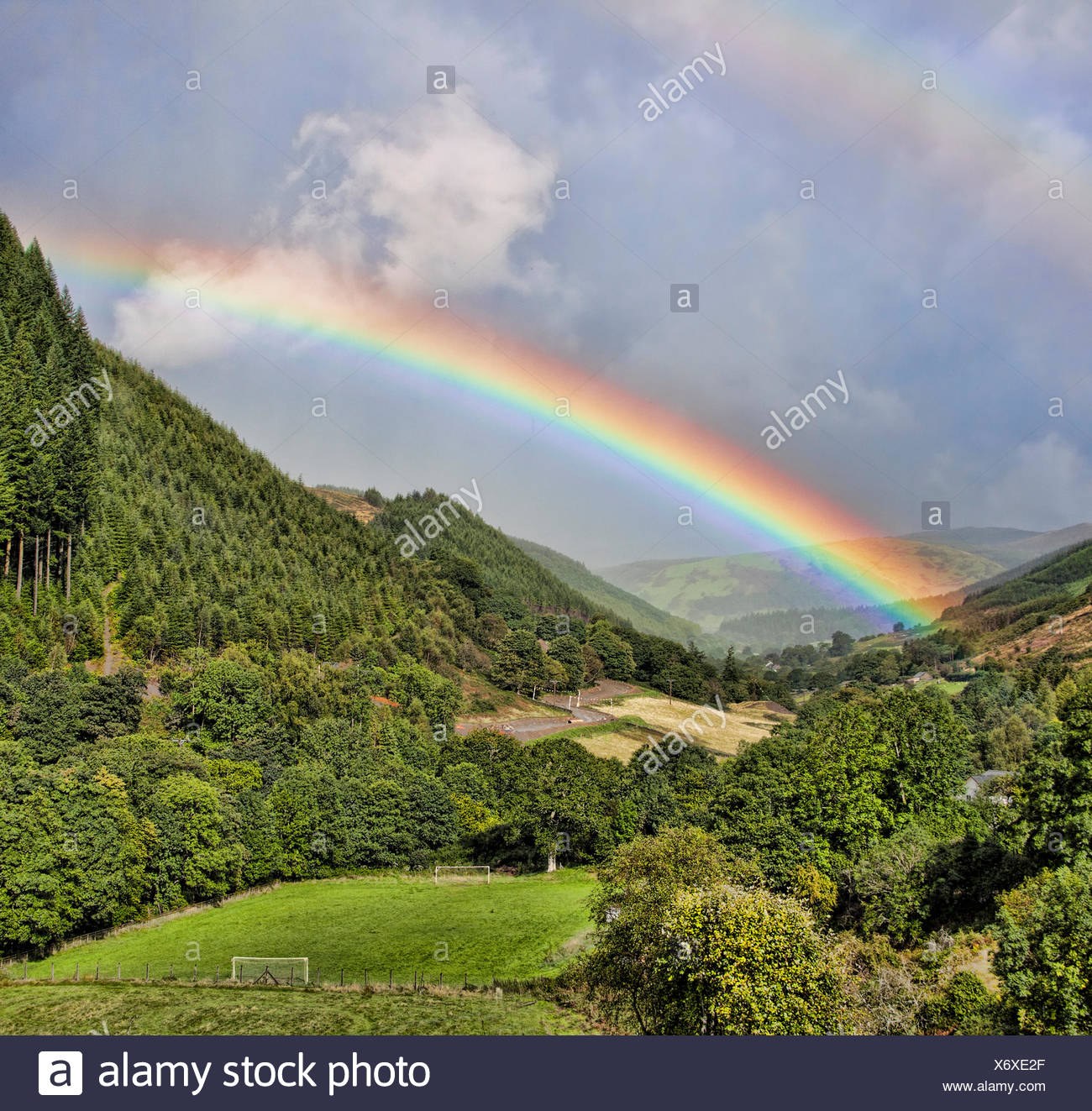 View of double rainbow above valley - Stock Image