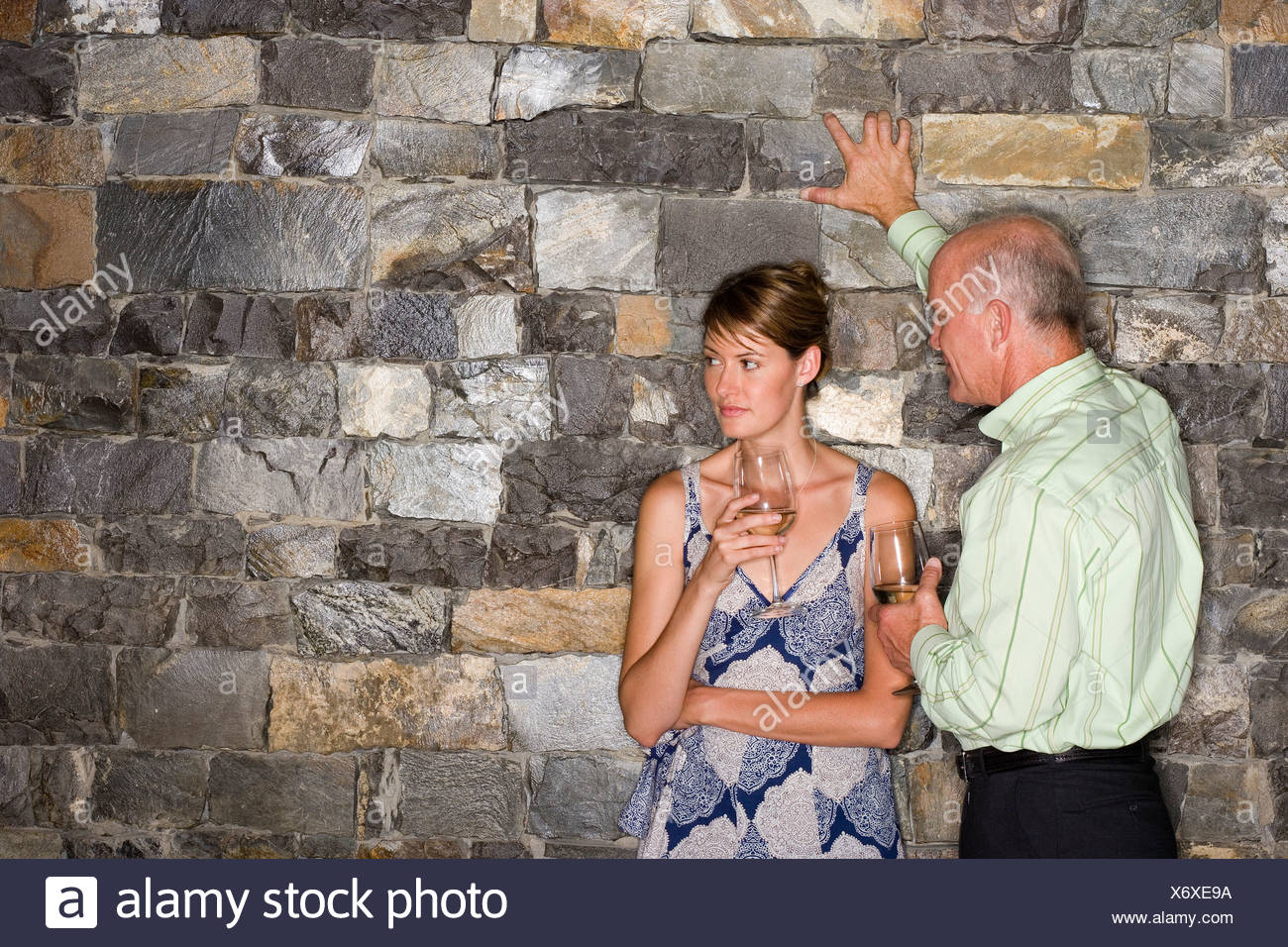 Mature man flirting with younger woman beside stone wall holding glasses of white wine woman looking away - Stock Image
