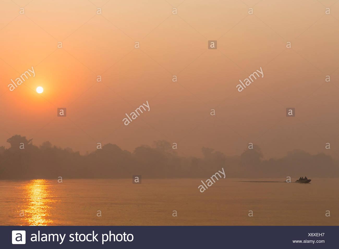 Brazil, Mato Grosso do Sul, Pantanal, Cuiaba River, Forest fire at sunrise - Stock Image