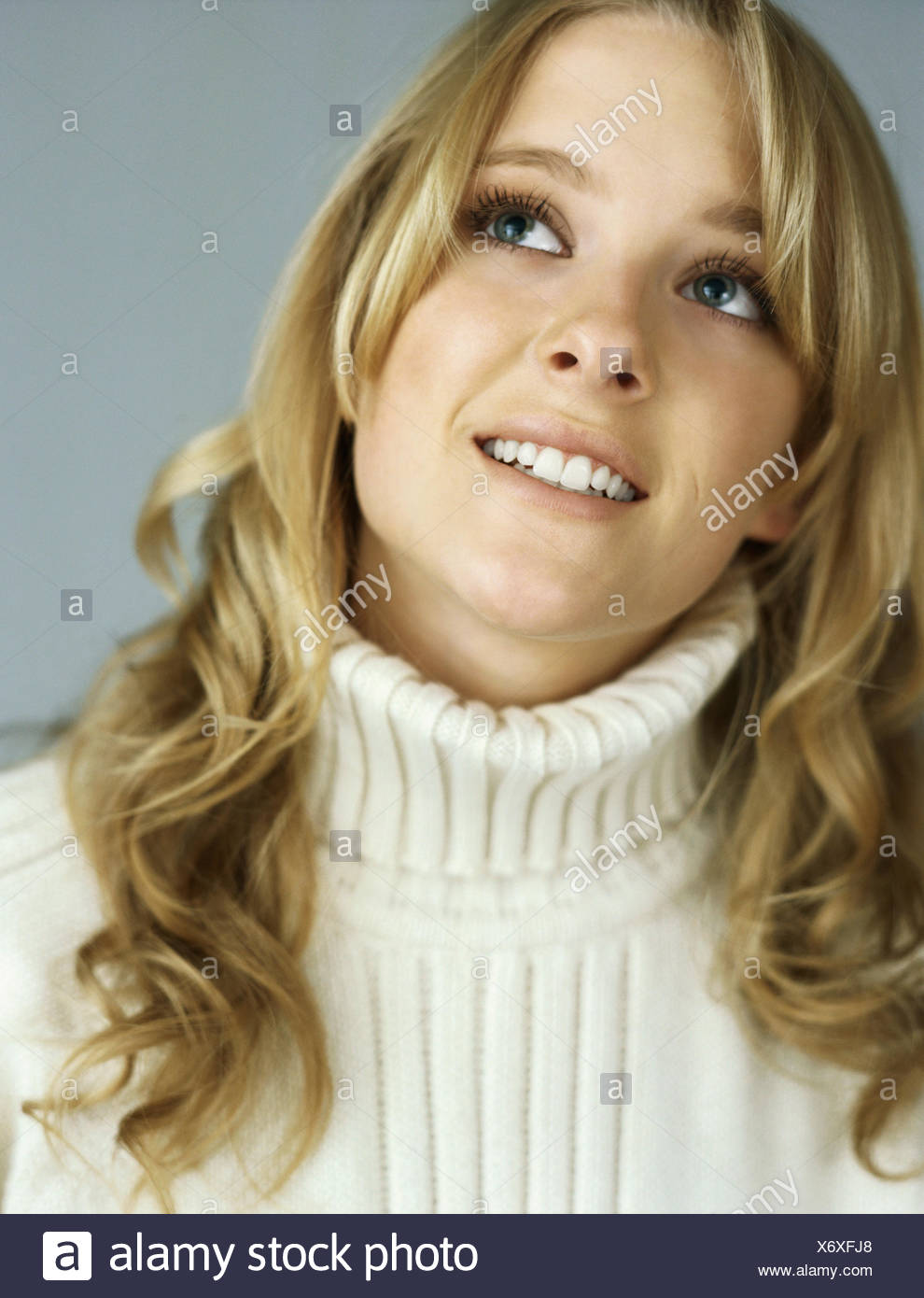 Teenage girl looking up in thought, portrait - Stock Image