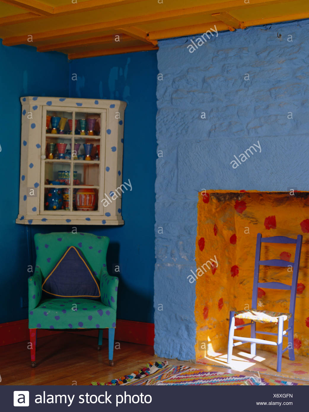 brightly painted furniture. Turquoise Upholstered Armchair Below Cupboard In Brightly Painted Eclectic Room With Blue Walls And Orange Fireplace Furniture F