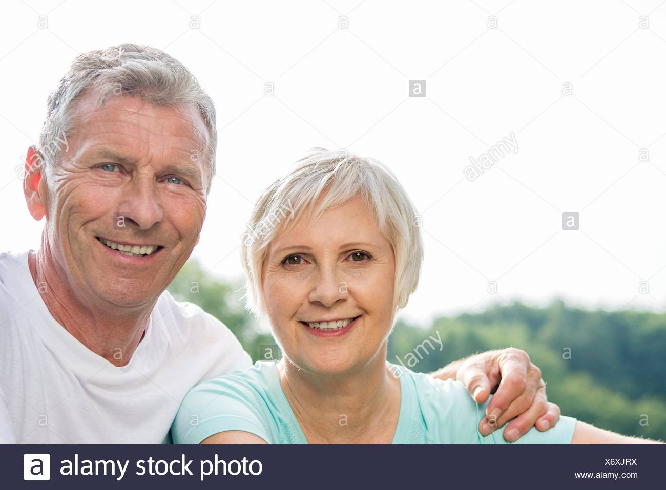 MODEL RELEASED. Senior couple smiling towards camera, man with arm around woman. Stock Photo