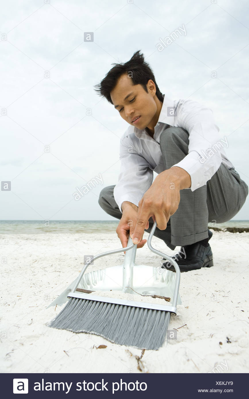 Man crouching on beach, sweeping sand into dustpan, low angle view - Stock Image