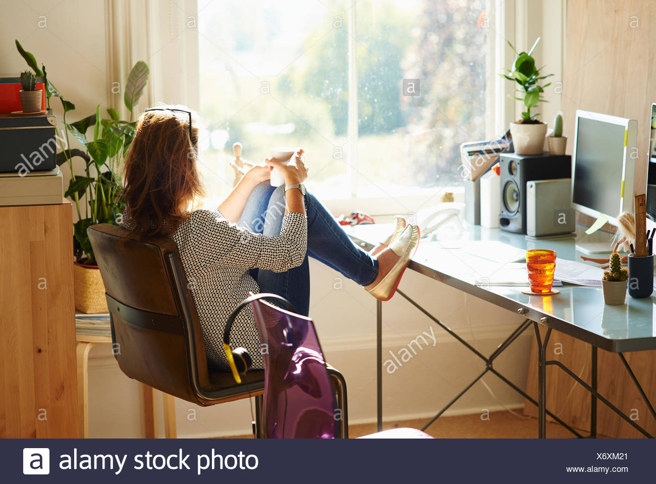 Pensive woman looking through window with feet up on desk in sunny home office - Stock Image
