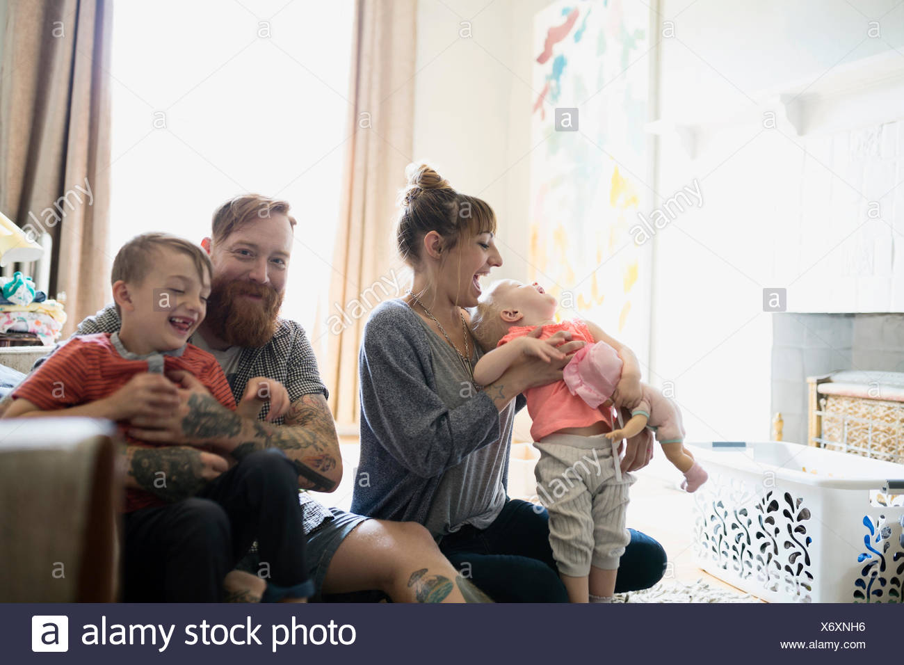 Happy young family in living room - Stock Image
