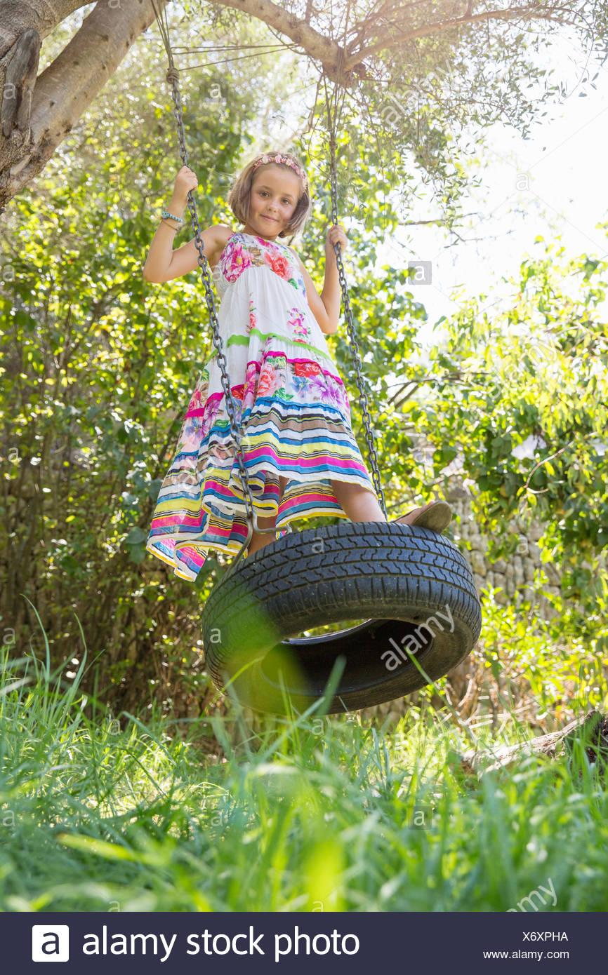 Portrait of girl standing swinging on tree swing in garden - Stock Image