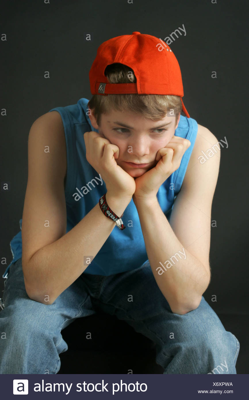 A boy sits there sad - Stock Image
