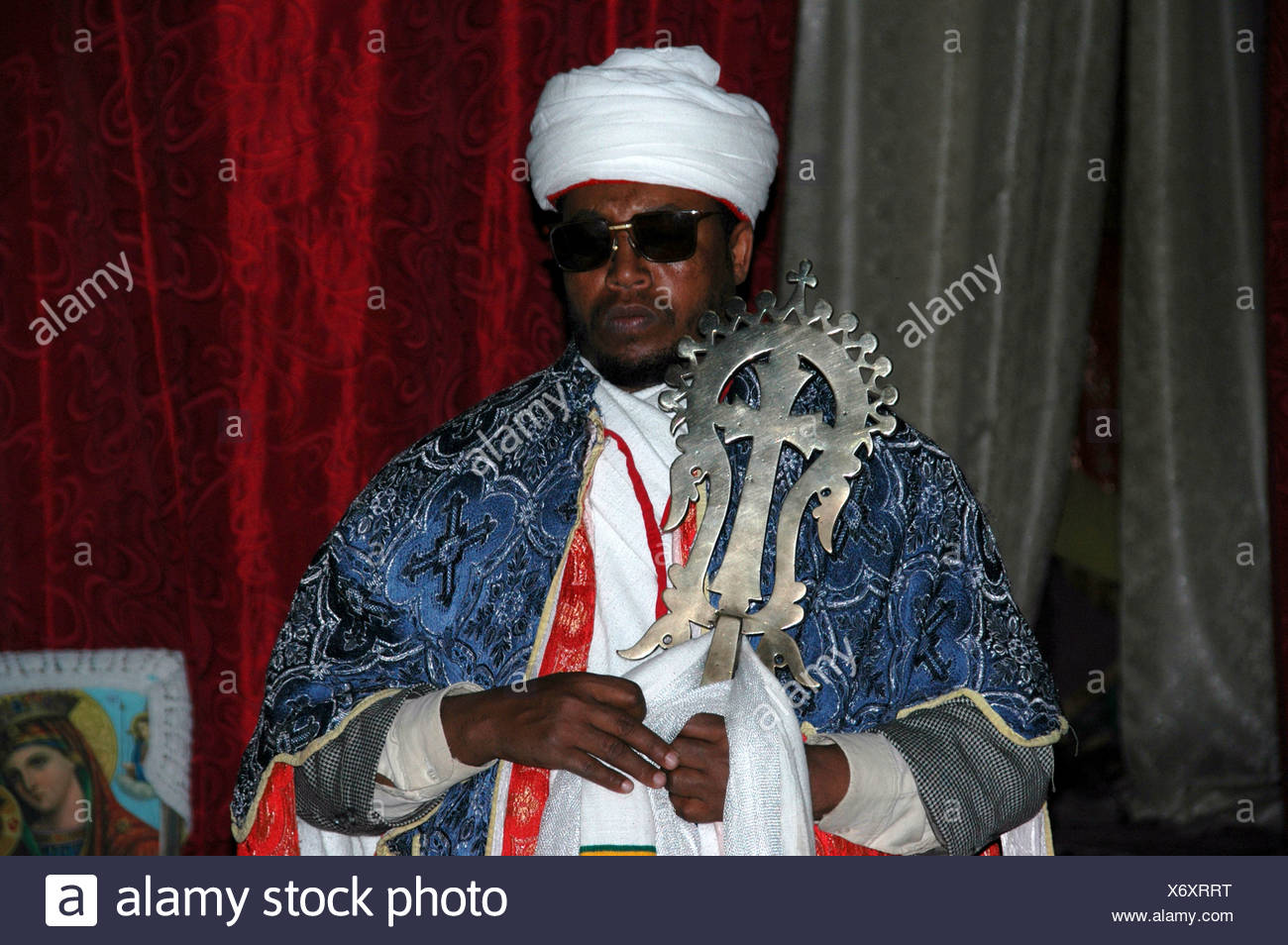 Priest wearing a white turban and cape carrying the Lalibela cross of gold, Beta Medhane Alem rock church, Lalibela, Ethiopia,  - Stock Image