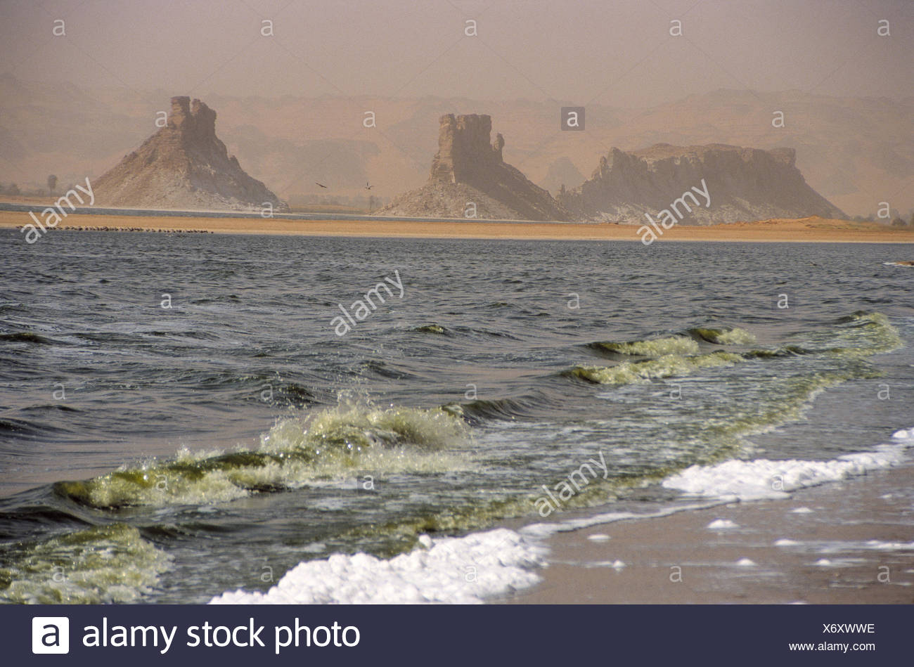 Chad, mesa country Ennedi, salt lake Ounianga Serir, Central, Africa, landlocked country, Sahara, Sahara waters, lake, 381 m sea level, beach, surf, mountains, mesas, bile formations, scenery, nature, foggy, haze - Stock Image