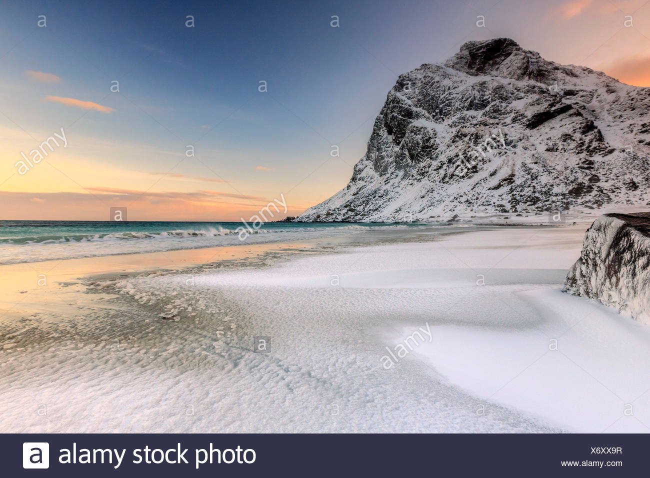 Waves advances towards the shore of the beach surrounded by snowy peaks at dawn. Uttakleiv Lofoten Islands Norway Europe - Stock Image