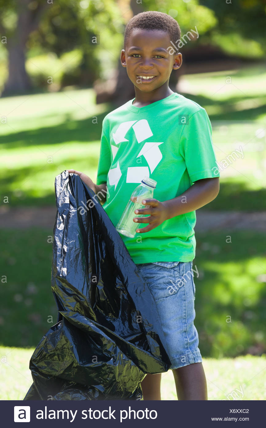 Young boy in recycling tshirt picking up trash - Stock Image