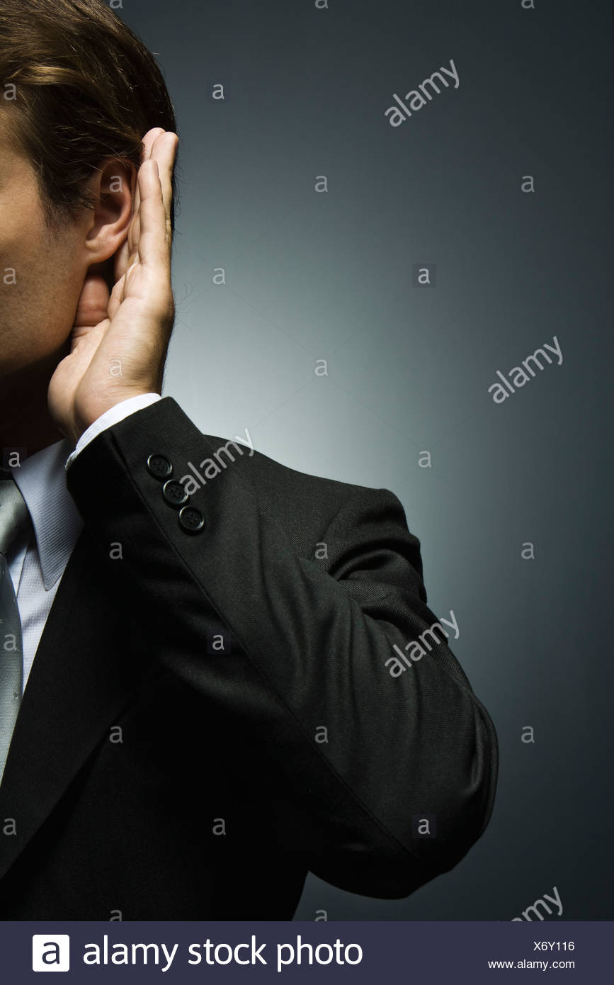 Man with hand cupped around ear listening attentively Stock Photo