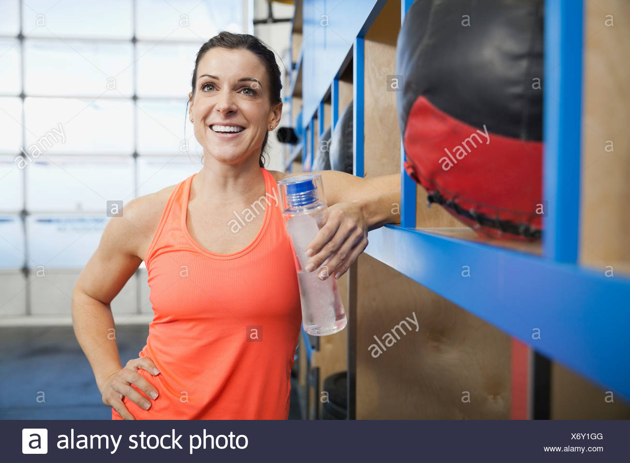 Woman holding water bottle in gym - Stock Image