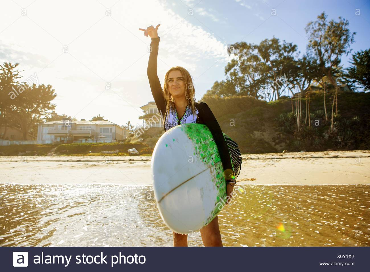 Young woman standing in sea, looking out to sea, holding surfboard, gesturing with hand - Stock Image