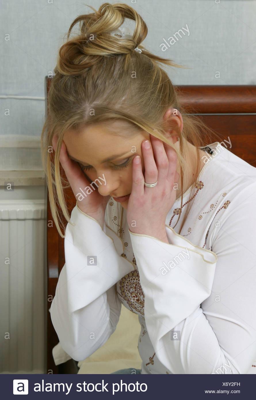 Young woman upset head in hands in bedroom headãndshoulders Stock Photo