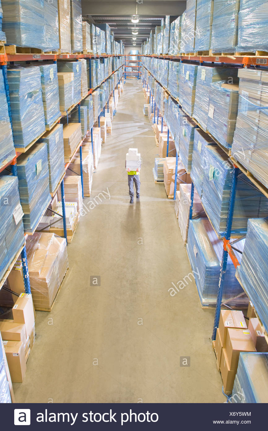 Warehouse worker carrying boxes in aisle Stock Photo