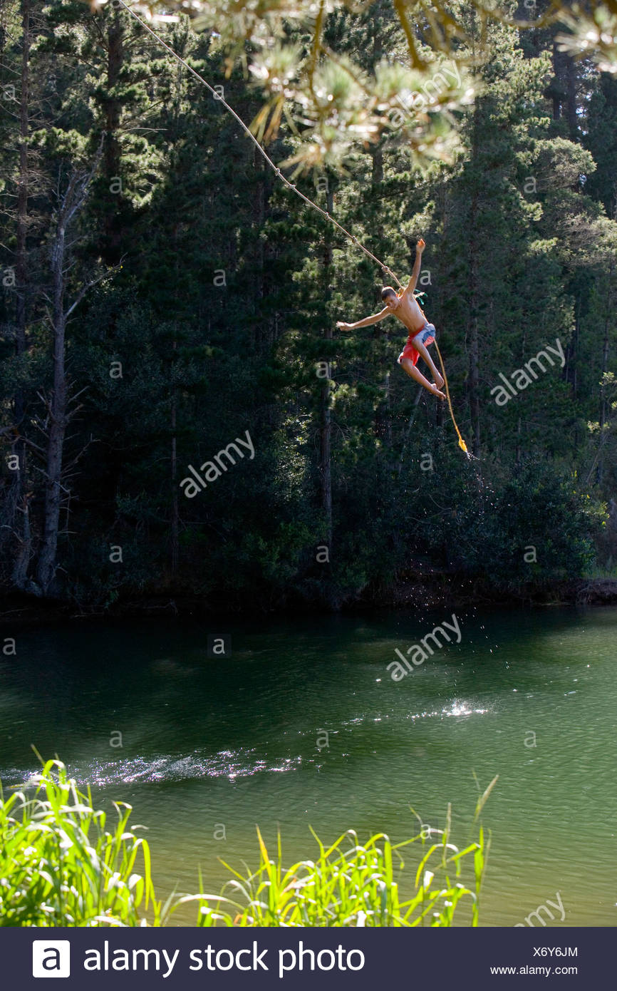 Boy 9 11 in swimming shorts letting go of rope swing above lake - Stock Image