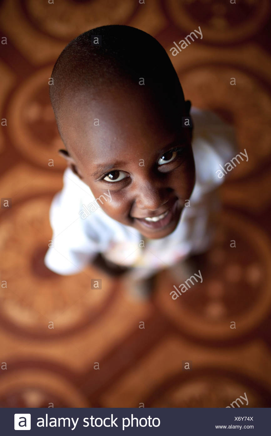 little boy standing on a tiled floor looking up at the camera over his head with a smile, Burundi, Bujumbura Mairie, Bujumbura - Stock Image