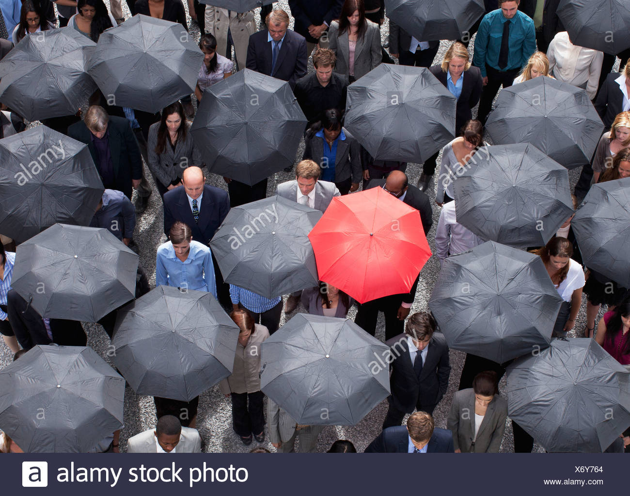 Red umbrella standing out in crowd of business people - Stock Image