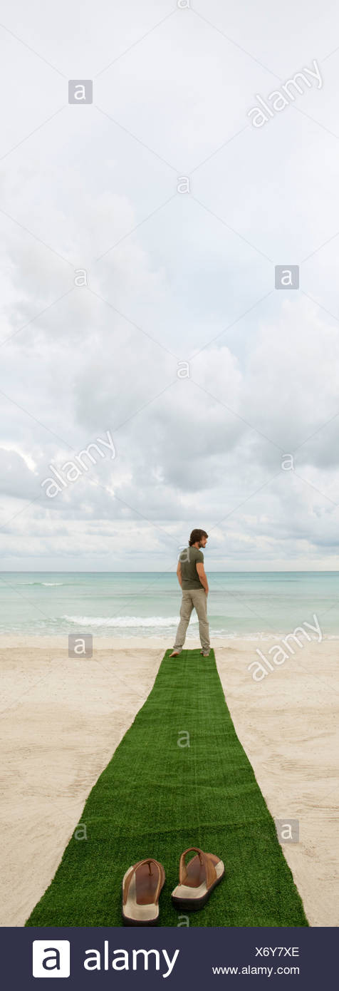 Man standing at end of carpet on beach, sandals on foreground - Stock Image