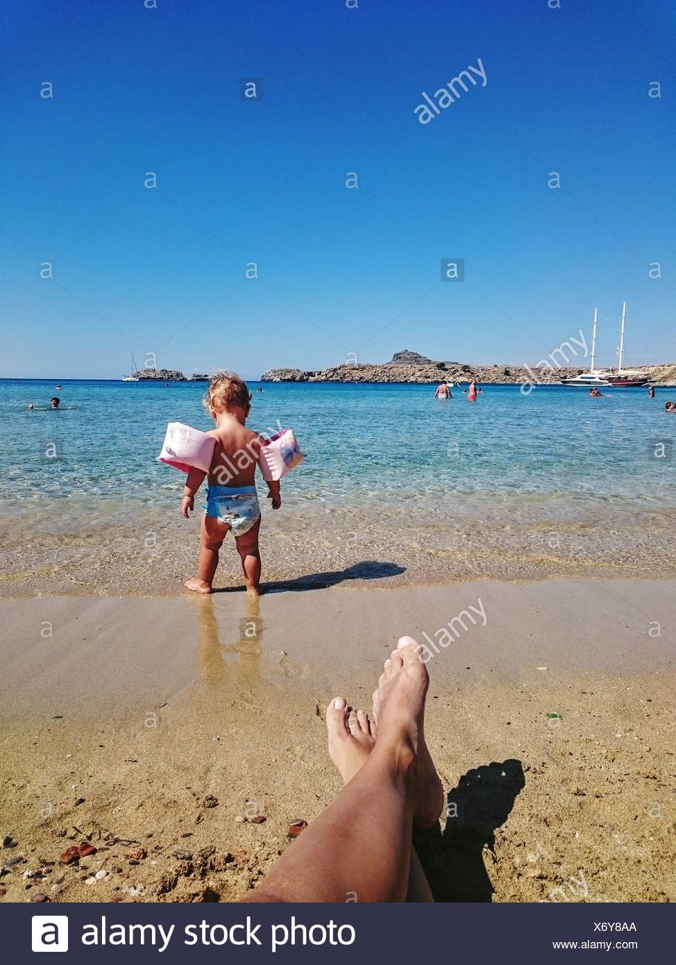Cropped Legs Of Man In Front Of Child Wearing Water Wings By Sea Against Sky - Stock Image