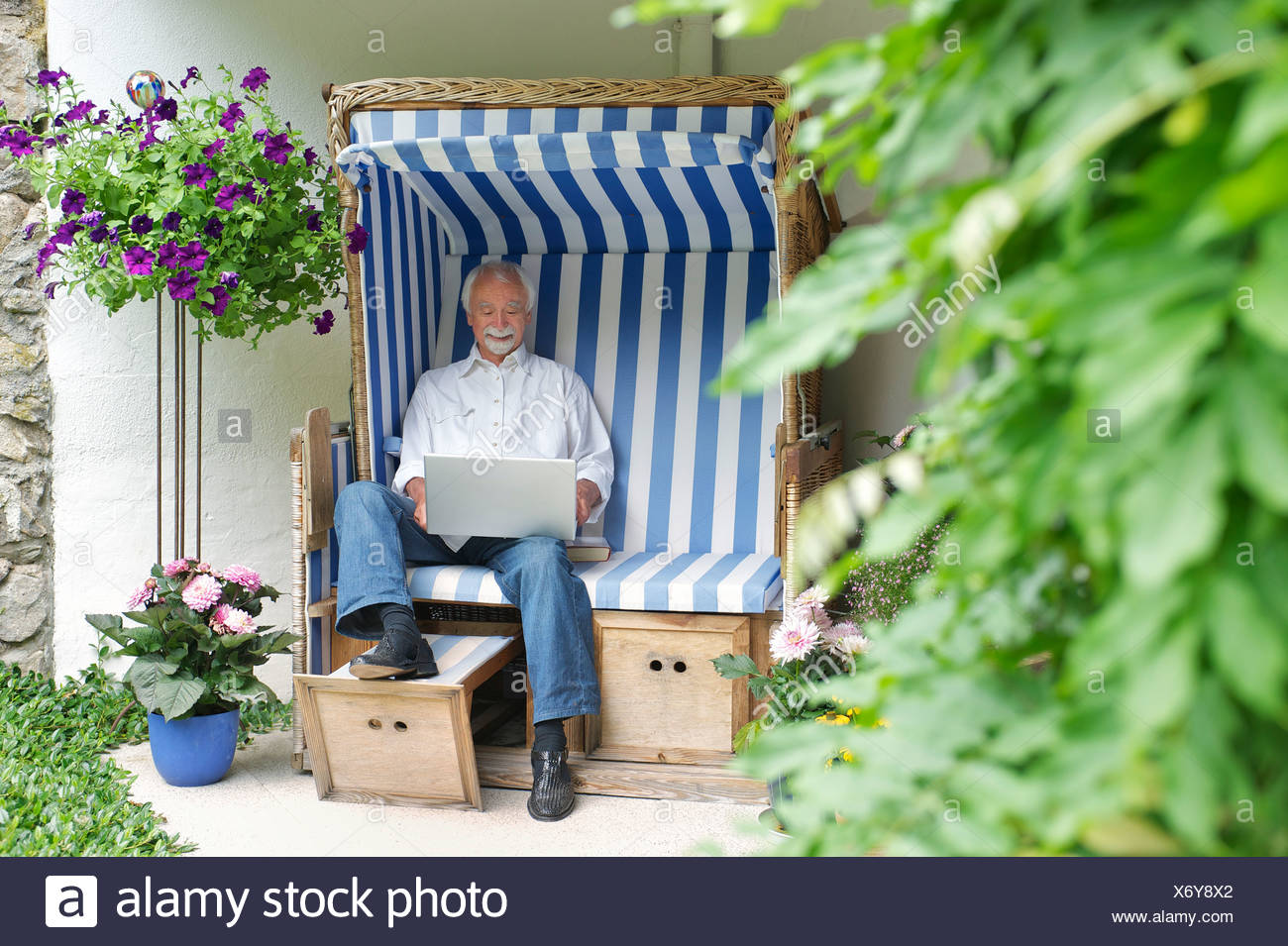 Senior man using laptop on garden seat - Stock Image