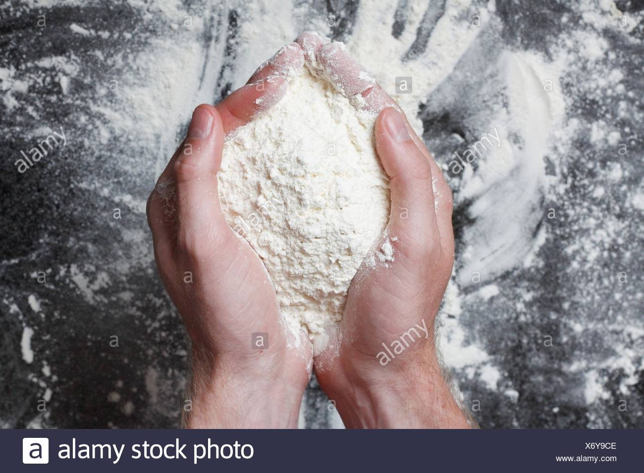 Hands holding white wheat flour - Stock Image
